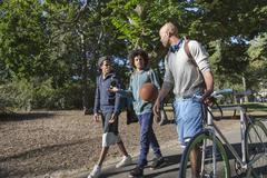 Young men walking in park, one pushing bike - stock photo