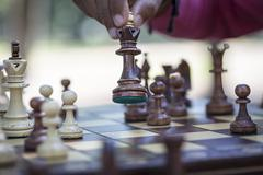 Hand moving chess piece on board, close up Stock Photos