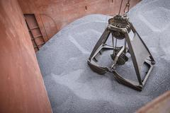 Grab unloading metal alloy from ship's hull Stock Photos