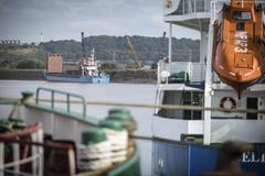 Small bulk load ship on river, view from port - stock photo