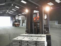 Fork lift driver transporting metal alloy in port store Stock Photos