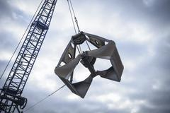 Low angle view of crane grab against cloudy sky - stock photo