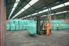 Workers and fork lift truck in bulk fertiliser store in port Stock Photos