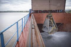Grab unloading metal alloy from ship's hull - stock photo