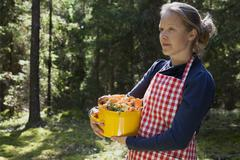 Woman in forest with mushrooms in saucepan Stock Photos