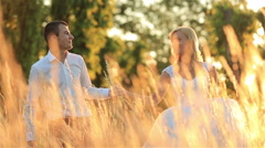 Young beautiful wedding couple walking in a golden wheat field. Wonderful sunset Stock Footage
