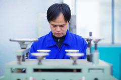 Worker at small parts manufacturing factory in China, looking down Stock Photos