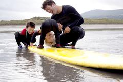 Father and sons playing with surfboard - stock photo