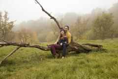 Young couple sitting on bare tree in misty park Stock Photos