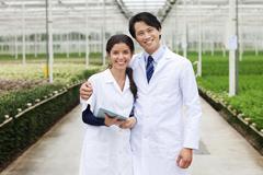 Scientists in greenhouse, arm around Stock Photos