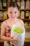Girl holding bag of confectionery - stock photo