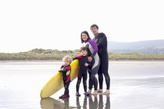 Family with two boys and surfboard on beach - stock photo