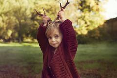 Toddler using sticks as antlers Stock Photos