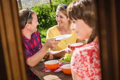 Friends breakfasting at table outside chalet, Tyrol, Austria - stock photo
