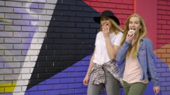 Young Women Look At Camera, As They Walk, Take A Bite Of Their Donuts In Unison Stock Footage