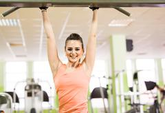 Sport, fitness, bodybuilding, teamwork and people concept - young woman flexing Stock Photos
