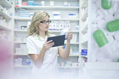Pharmacist looking at digital tablet and medication Stock Photos