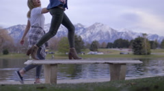 Girl Jumps Up And Walks Across Park Bench, Her Friend Helps Her Balance Stock Footage
