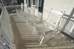 Weathered White Rocking Chairs On A Dirty Porch - stock photo