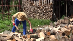 Tired man chop firewood and drink water from plastic bottle. 4K Stock Footage