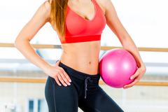 Beautiful athletic waist of a young girl with  pink ball in hand the gym Stock Photos