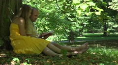 Couple man and woman on a romantic date vacation reading a book under old tree Arkistovideo