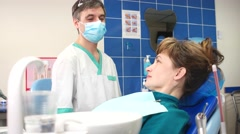 Happy doctor dentist talking to a satisfied patient at the hospital. Stock Footage