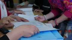 Voter signing and taking ballot for voting, focus on ballot papers, close up. - stock footage