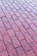Red cobblestones moist with water after a rain shower. Copy space background  - stock photo