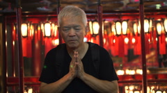 Asian senior man pray in temple with hands clasped in Chinese temple - stock footage