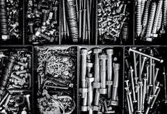 Piles of nuts, bolts, and washers create an industrial themed background. Squ Stock Photos