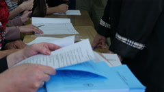 Election commission establishing identity of voter,hands holding ballot close up Stock Footage
