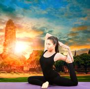asian woman health care yoga posting with asian ancient pagoda temple and sun - stock photo