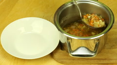 Vegetable soup ladle is poured into a bowl Stock Footage