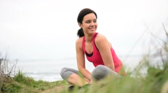 Woman in fitness outfit relaxing after exercising Stock Footage
