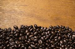 Roasted coffee beans scattered on a wooden table Stock Photos
