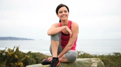 Woman in fitness outfit relaxing after exercising - stock footage