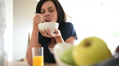 Mature woman eating cereals for breakfast - stock footage