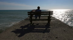 A woman sits on a pier at a beach Stock Footage