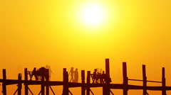 U-Bein teak bridge at sunset on lake, Mandalay Stock Footage
