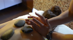 Masseuse using hot stone massage therapy Stock Footage