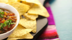 Fresh salsa in white bowl with white corn tortilla chips. - stock footage