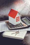 Real estate investment. House, key and calculator on table - stock photo