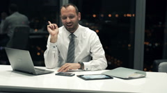 Businessman with tablet and laptop thinking and having great idea in office Stock Footage