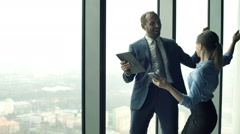 Successful businesspeople with tablet  and smartphone find great news in office - stock footage