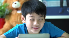 4k, Young asian boy browsing the internet on a digital tablet at home. Stock Footage