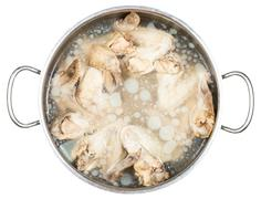 stewpan with cold boiled chicken wings in broth - stock photo