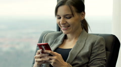 Happy businesswoman with smartphone sitting on armchair by the window in office - stock footage