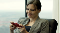Happy businesswoman playing game on smartphone sitting on armchair by the window Stock Footage