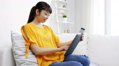 Happy asian woman with tablet pc and credit card Stock Footage